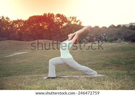Woman practicing yoga pose outdoors over sunset sky background. Woman doing yoga poses outdoors at sunset with lens flare. Female fitness training outdoor. Healthy lifestyle image of woman outside. - stock photo