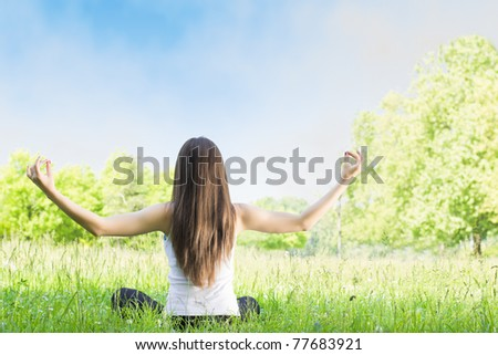 Woman practicing yoga postures back outdoors.