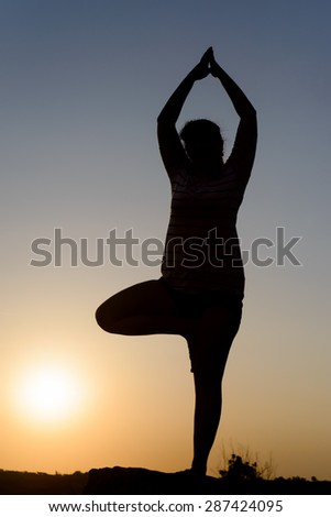 Woman practicing yoga standing balanced on one leg as she meditates in nature silhouetted at sunset by the fiery glow of the orange sun, with copyspace - stock photo