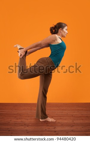 Woman practicing yoga stretches her leg backwards