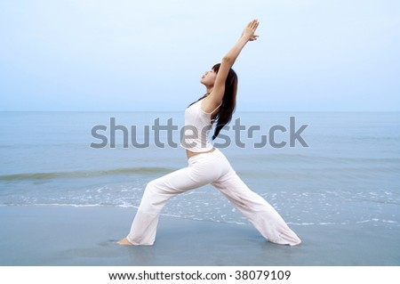 Woman practicing Yoga (Warrior Position) on the beach. - stock photo