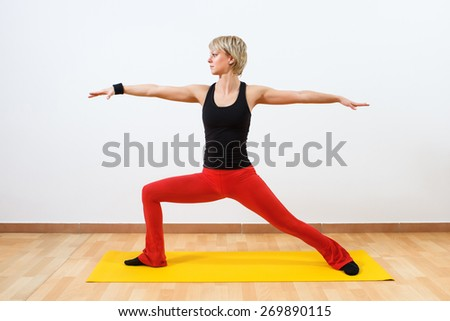 Woman practicing yoga. Yoga-Virabhadrasana /Warrior pose  - stock photo