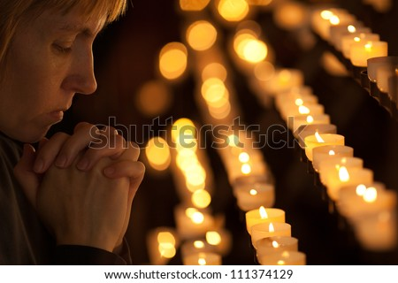 Woman praying in Catholic church - stock photo