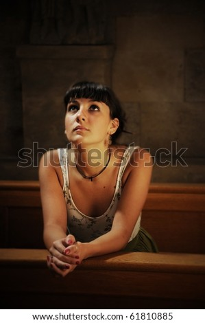 Woman praying in the church - stock photo