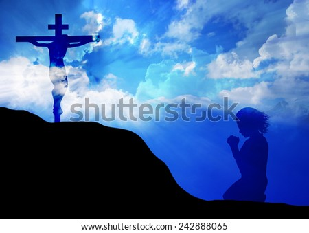 Woman praying under the cross - stock photo