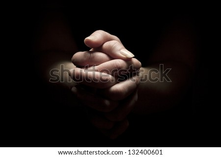 Woman praying with hands folded to God.