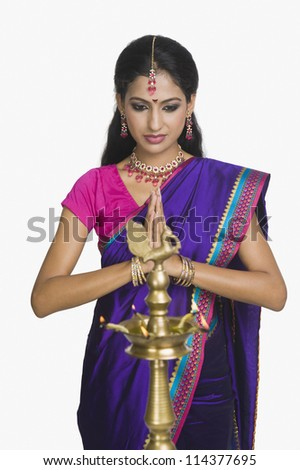 Woman praying with oil lamp in front of her