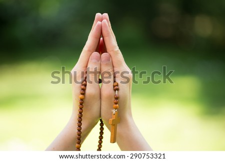 woman prays with a rosary in hands - stock photo