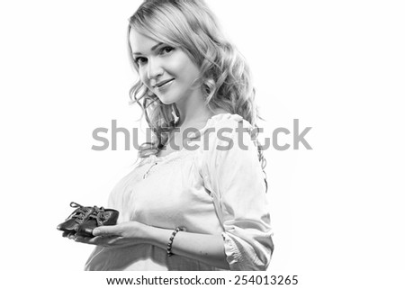 woman pregnant holding shoes. Black and white - stock photo