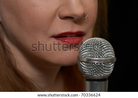 Woman prepares to sing live - closeup of microphone and mouth - stock photo