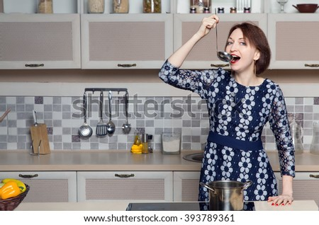Woman prepares vegetable soup in his kitchen. Emotional young woman in evening dress tries to cook for the first time.Woman cooking in the kitchen. To cook dinner. - stock photo
