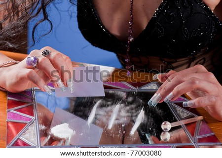 Woman preparing a line of cocaine on a fancy mirror - stock photo