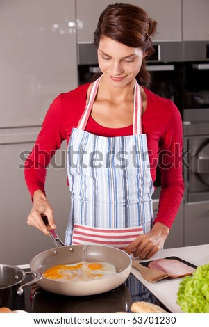 Woman preparing an egg in a frying pan
