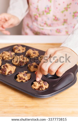 Woman preparing baking chocolate chip muffin closeup