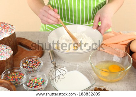 Woman preparing Easter cake in kitchen - stock photo
