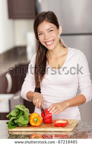 Woman preparing food in kitchen making salad smiling happy. Beautiful mixed race Caucasian / Asian female model home in kitchen. - stock photo