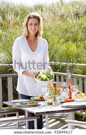 Woman preparing meal outdoors - stock photo