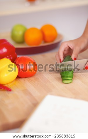 Woman preparing salad in the kitchen - stock photo