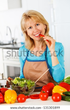Woman preparing salad in the kitchen. Healthy Eating. - stock photo