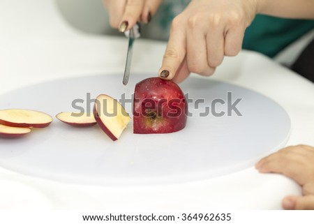 Woman preparing salad with an apple with a kitchen knife