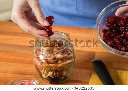 Woman preparing sweet preserves and arranging mix of dried fruits into a jar - plums, walnuts, apricots, figs, cranberries. - stock photo