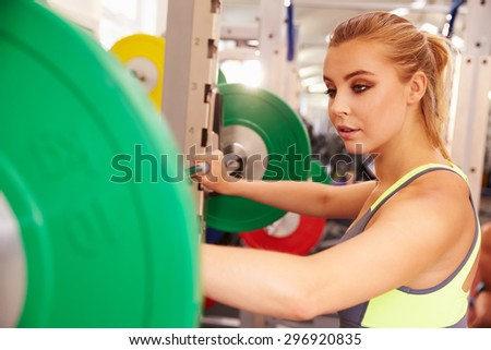 Woman preparing to lift barbells at a squat rack in a gym - stock photo