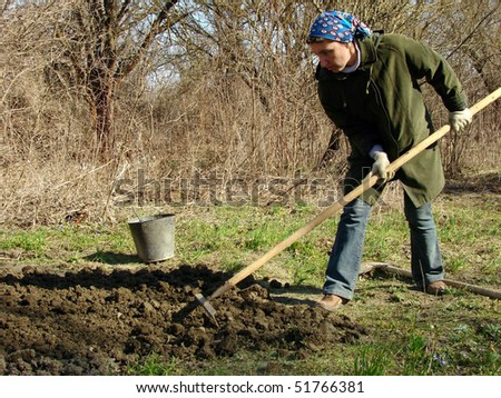 woman preparing vegetable bed for planting at the early springtime