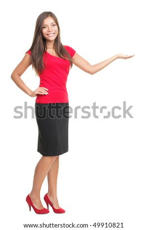 Woman presenting product isolated on white. Happy cheerful full length portrait of a beautiful mixed Asian / Caucasian young woman model holding her arm out and showing copy space for your product. - stock photo