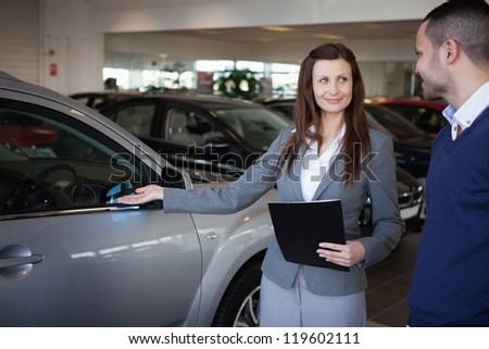 Woman presenting something to a man in a dealership - stock photo