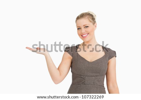 Woman presenting something with her hand against white background - stock photo