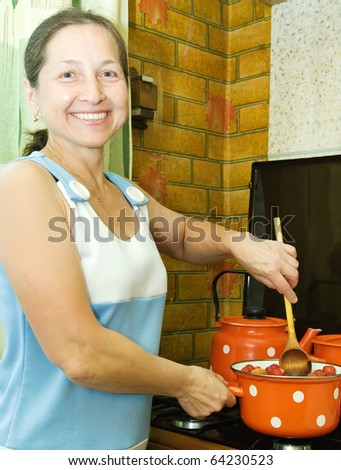 Woman preserving home-made jam from  strawberries in kitchen - stock photo