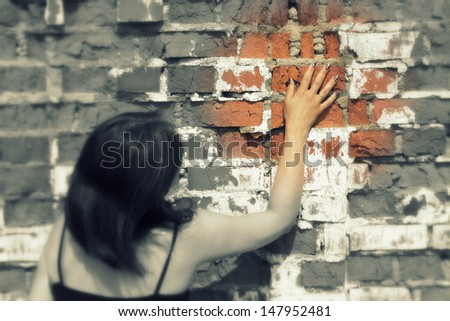 woman pressed against the brick wall and touched her hand