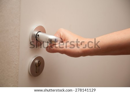 woman pressing door handle of house or appartment