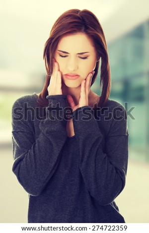 Woman pressing her cheek because of toothache - stock photo