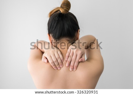 Woman pressing her hand on painful shoulder. Pain in the human body - stock photo