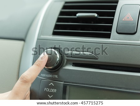 woman pressing radio button in car