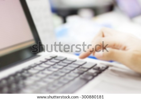 Woman pressing the button on laptop computer keyboard. Blue toned image.