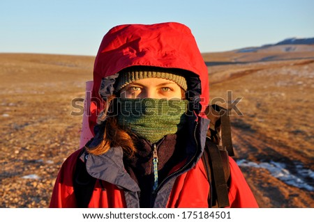 woman protecting face from a cold in the mountains  - stock photo