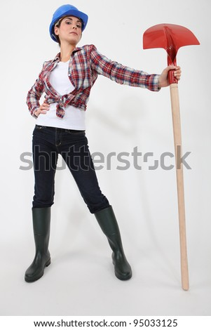 Woman proudly holding spade - stock photo