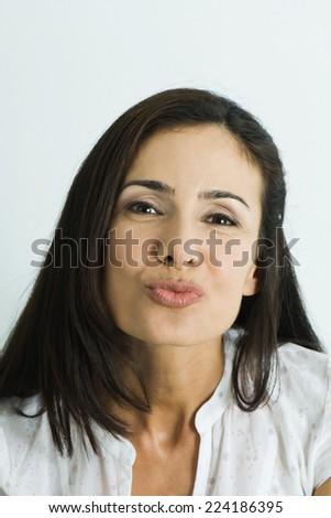 Woman puckering lips, looking at camera, portrait - stock photo