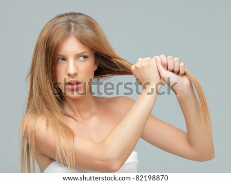 woman pulling damaged hair with both hands - stock photo