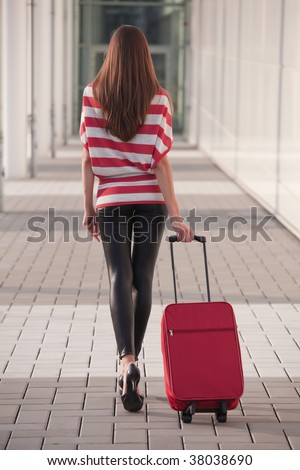 woman pulling her luggage on the street - stock photo