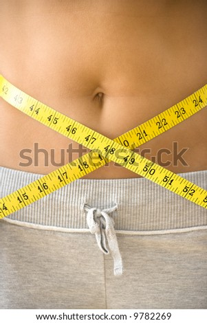 Woman pulling measuring tape around bare waist. - stock photo