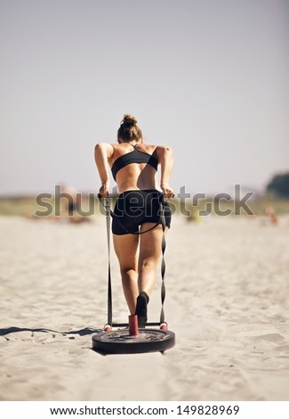 Woman pulling sled during a beach workout - stock photo