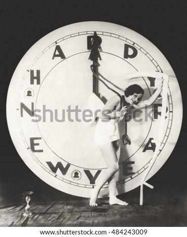 Woman pulling the hour hand of giant clock on New Year's Eve
