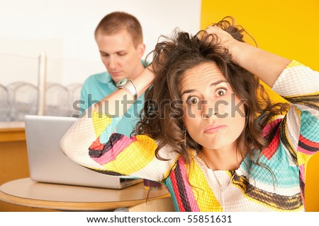 Woman pulls at her hair in frustration while her boyfriend works on a laptop in the background.  Horizontal shot. - stock photo
