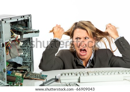 Woman pulls her hair out over her broken computer - stock photo