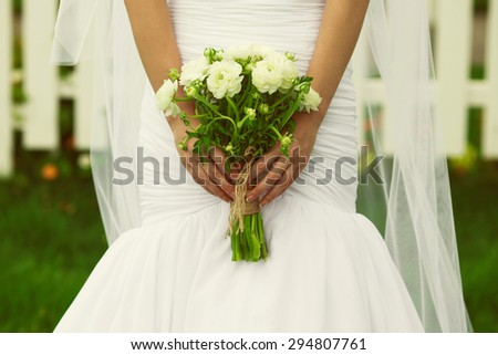 Woman purity concept. Bride's hands holding bouquet over white vapory dress and white fence, green garden. Country vintage style. Close up. Outdoor shot - stock photo