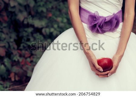 Woman purity concept. Bride's hands holding red apple - symbol of love - over white vapory dress and green garden. Vintage style. Close up. Copy-space. Outdoor shot - stock photo