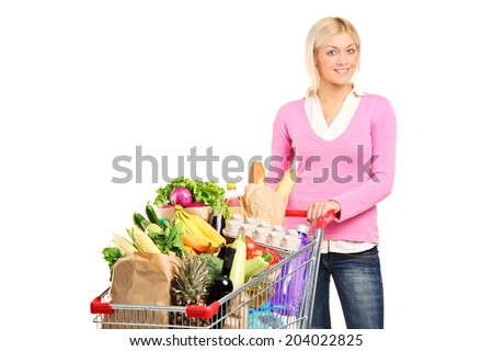 Woman pushing a shopping cart full of groceries isolated on white background - stock photo